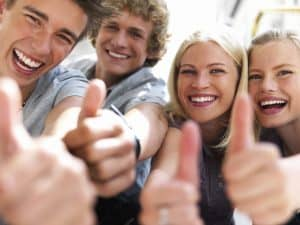 2 men and 2 women smiling with thumbs up after receiving Chiropractic care